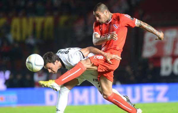 Pablo Ledesma se la juega de cabeza ante la entrada de Jesús Méndez. (Foto: Télam)