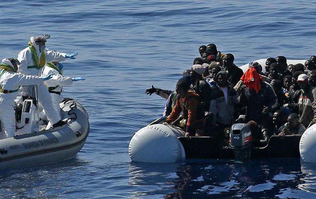 Un bote inflable sobrecargado de migrantes recibe auxilio en las aguas italianas. Salen de Libia
