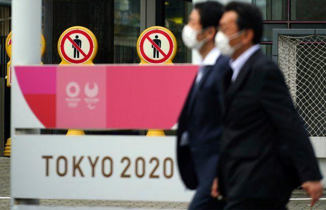 La gente camina junto a los carteles que promocionan los Juegos Olímpicos y Paralímpicos de Tokio 2020.
