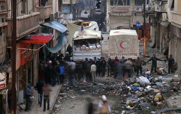 Misión peligrosa. Camiones de la Media Luna Roja descargan víveres y medicinas en el destruido centro de Homs.