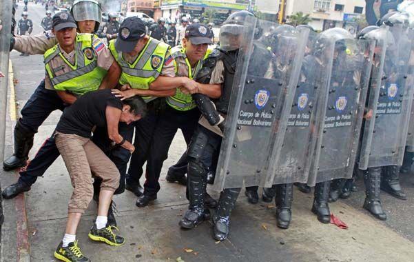 Polarización. Una joven intenta atravesar sin suerte una barrera policial.