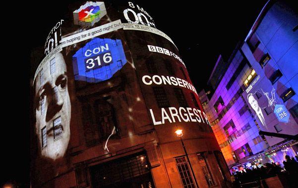 ¿ganador? El rostro de Cameron y el número de bancas que lograría en el panel luminoso de la BBC en Londres.