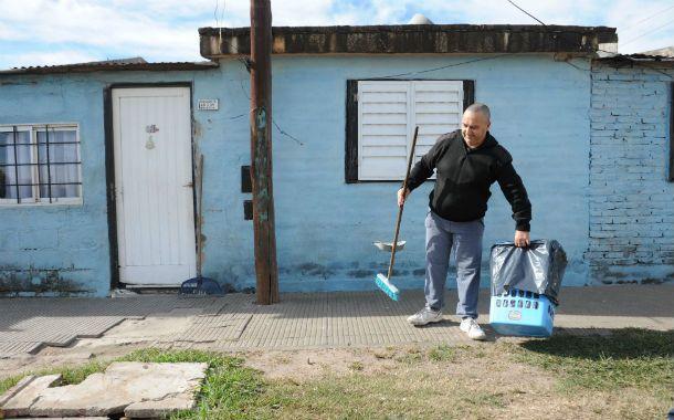 """Viejas costumbres. Un vecino limpia la vereda en el corazón de Las Flores. """"Antes vivíamos encerrados"""""""