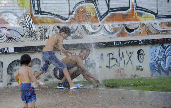 Todo vale. Los chicos buscaron ayer refrescarse con un chorro de agua junto a los galpones del Centro de la Juventud. (foto: Silvina Salinas)