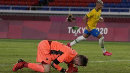 El arquero alemán, Florian Mueller se arrodilla tras el tercer gol del brasileño Richarlison, que sale a festejarlo.