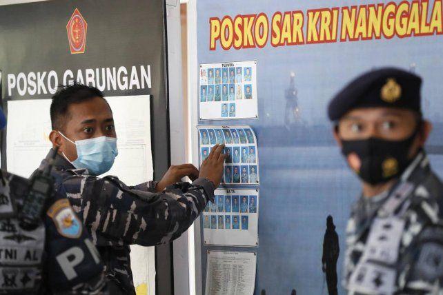 Un marino indonesio exhibe en la sala de prensa las fotos de los 53 tripulantes del Nanggala.