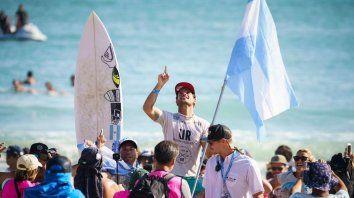 La bandera de Argentina en la mano, fuerte. Muñiz decidió representar a nuestro país pese a haberse criado en Brasil y le dio un nuevo título mundial en surf. (Foto twitter)