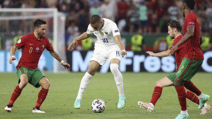 El francés Mbappe maniobra ante tres futbolistas de Portugal en la Eurocopa.