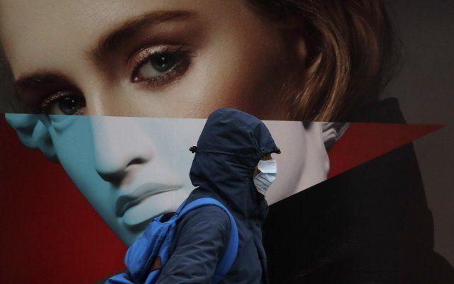 Un hombre con máscara facial pasa junto a un cartel publicitario en Londres