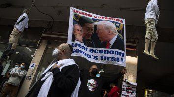 Los propietarios de pequeñas empresas ondean un cartel que muestra al presidente de Estados Unidos, Donald Trump, al presidente de China, Xi Jinping, y al primer ministro israelí, Benjamin Netanyahu, durante una manifestación contra la economía en Tel Aviv, Israel.