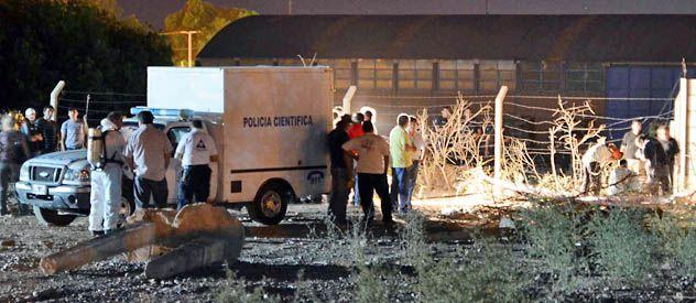 La policía científica abre la heladera arrojada en un baldío y retira el cadáver de Ariel Tapia.
