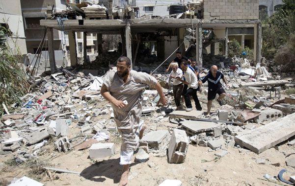 Vecinos ayudan a evacuar un herido de un edificio destruido por las bombas en la ciudad de Gaza.