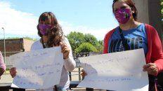 Dos mujeres sostienen carteles con respuestas a frases machistas, en la presentación de la campaña Lxs de afuera no somos de palo.