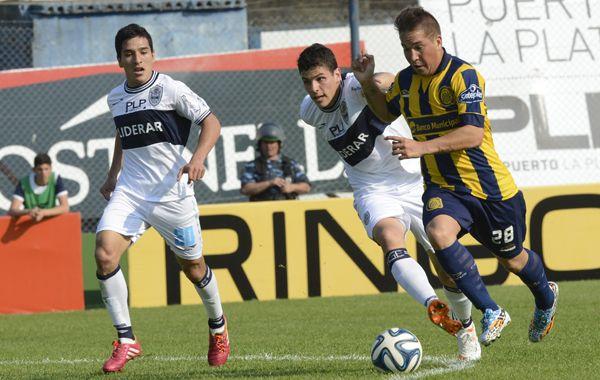 Cachete Acuña mete la diagonal de derecha a izquierda ante la marca de dos defensores de Gimnasia. (Foto: Sebastián Suárez Meccia)
