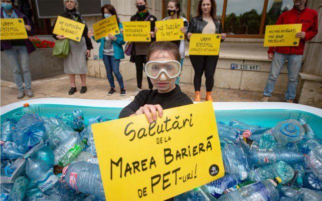 Un activista sostiene una pancarta que dice Saludos desde la Gran Barrera de PET en una piscina inflable llena de botellas de plástico frente al Ministerio de Medio Ambiente de Bucarest