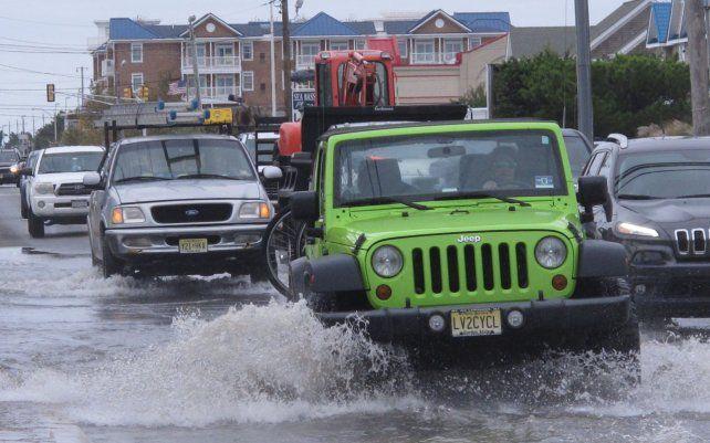 Vehículos cruzan una intersección inundada en la entrada de Long Beach Island en Ship Bottom