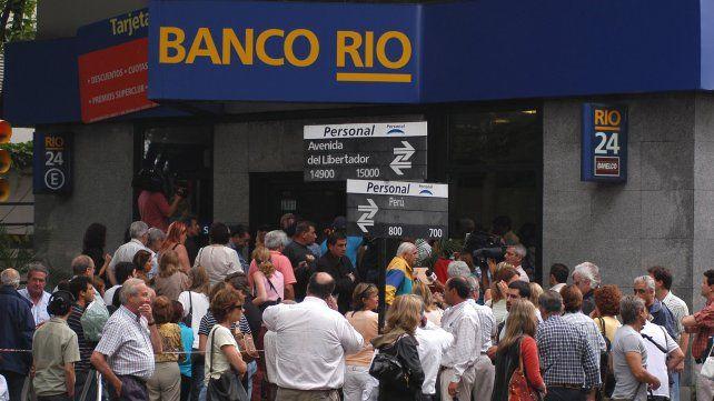 Los clientes del banco Río de Acasusso rodean alborotados la sucursal tras el cinematográfico robo.