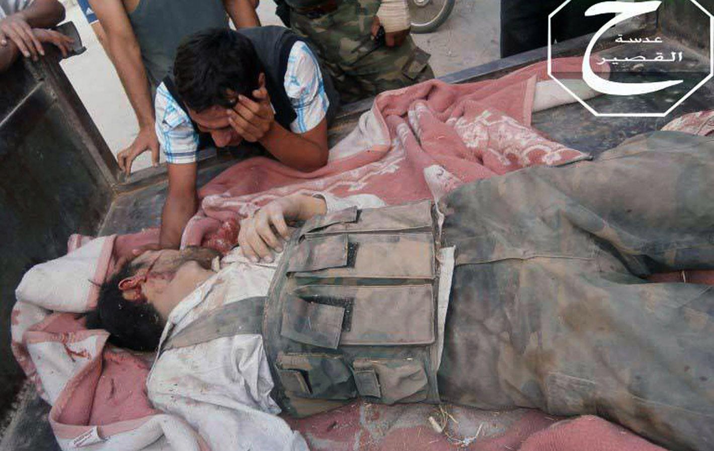 Sin tregua. El hermano de un rebelde sirio llora sobre su cadáver en la sitiada ciudad de Al Qusayr.