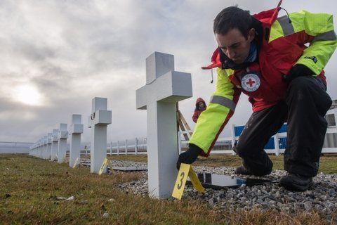 trabajo. Un forense de la Cruz Roja señala una de las tumbas de Darwin.