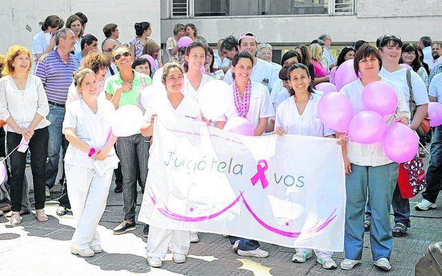 por el diagnóstico. Empleados de los efectores de salud posan con la bandera de la campaña oficial.