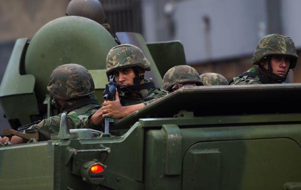 En guerra. Infantes de marina sobre sus blindados ingresan en la peligrosa favela carioca de Cajú.
