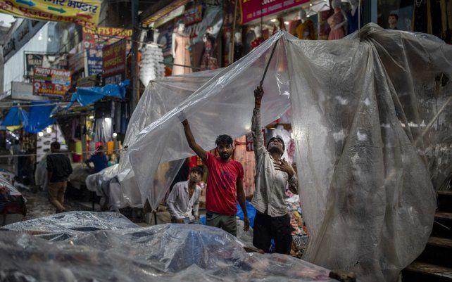 Vendedores ambulantes cubren sus puestos con polietileno mientras llueve en Noida