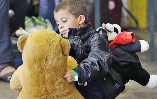 Atento. Un chico se toma un momento para ocuparse de su oso de peluche en la estación ferroviaria de Munich.