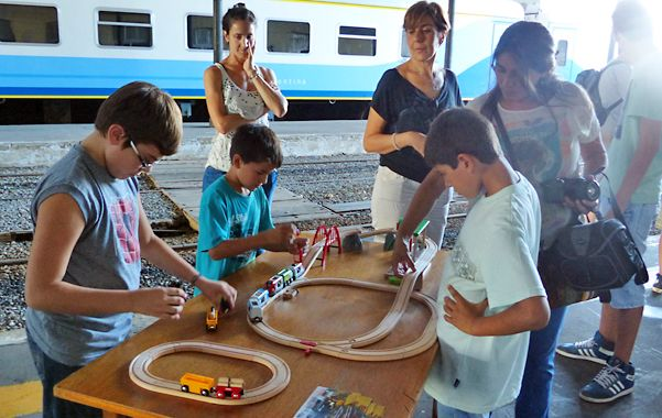 juegos e imágenes. Un grupo de chicos se divierte con trenes en escala.