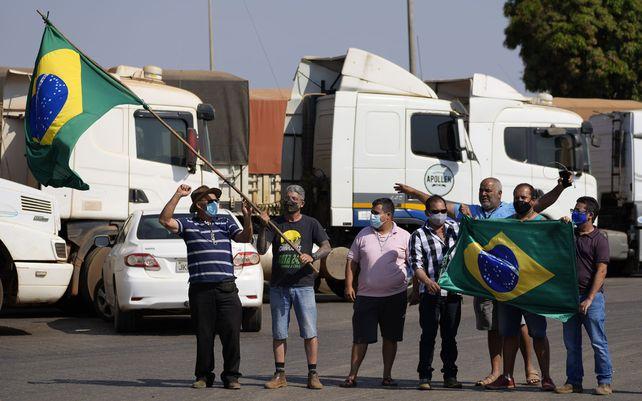 Conductores de camiones que apoyan al presidente brasileño Jair Bolsonaro ondean banderas reunidos en una gasolinera al sur de Brasilia, Brasil. Los camioneros siguen movilizados desde los festejos del Día de la Independencia.