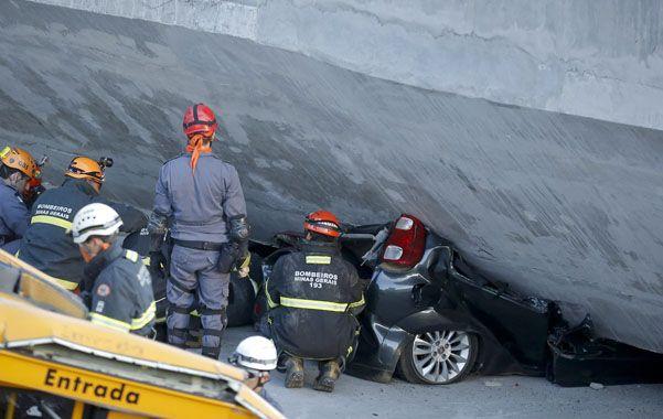 Espantoso. Un bombero trata de rescatar el cuerpo del ocupante de un auto aplastado por la mole de cemento.