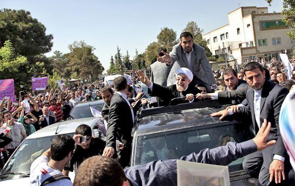 Alegría y protestas. Iraníes de línea dura lanzaron huevos y zapatos contra el vehículo que trasladaba a Rohani.
