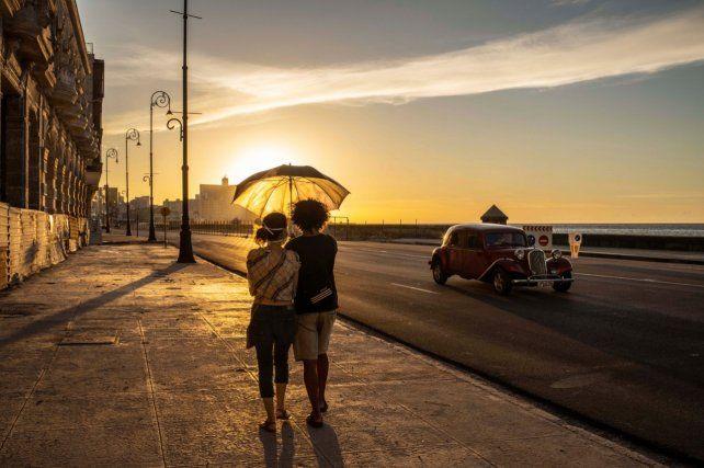 Una pareja usando barbijo como precaución camina por el Malecón.
