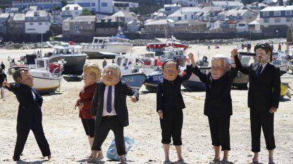 Parodia. Manifestantes ambientalistas se burlan de los gobernantes del G7 en las playas de Cornwall.