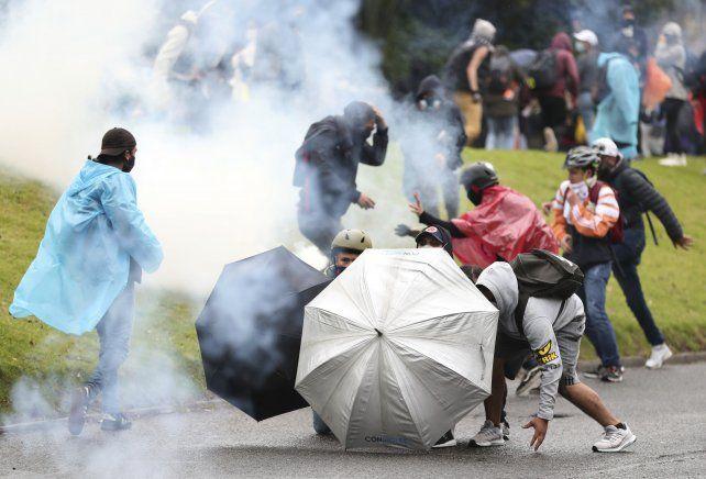 Manifestantes en Bogotá tratan de resistir a los lacrimógenos de la policía.