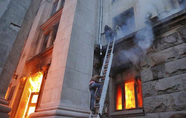 Tragedia. Civiles huyen por una escalera del edificio gremial envuelto en llamas en Odessa.