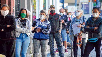 A la espera. Un grupo de rosarinos esperó ayer su turno para ingresar a un local de pago de impuestos utilizando el barbijo, tal cual lo dispuso el decreto del gobernador.