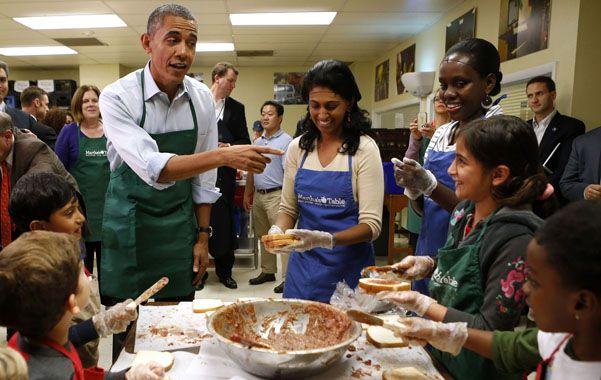 Distensión. Obama fue ayer a dar una mano en un centro de atención a indigentes de Washington.
