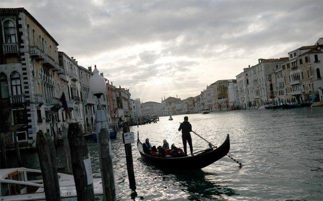 Gondoleros llevan a los turistas a lo largo del Gran Canal. Los países del G-7 dicen que están listos para tomar medidas para amortiguar los impactos económicos del nuevo brote de coronavirus.