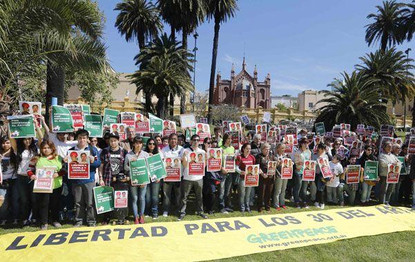 """Buenos Aires. Los manifestantes de Capital Federal parados detrás de una bandera en apoyo a """"los 30 del Artico""""."""