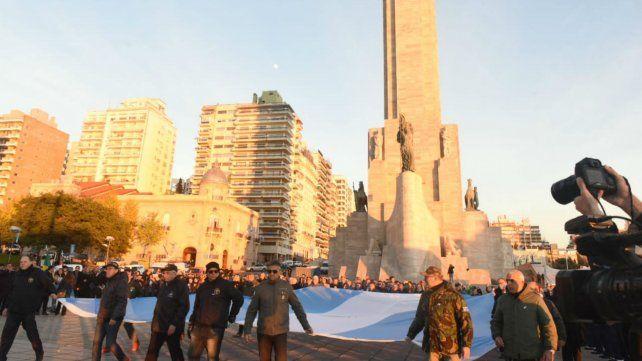 Los Veteranos de Malvinas llevan la bandera hasta el mástil mayor para el izamiento.