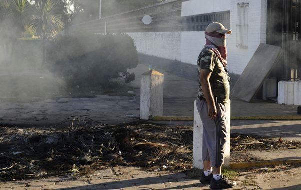 Sólo cenizas. Un policía que se había plegado a la huelga depone la actitud al lado de los restos humeantes del piquete.