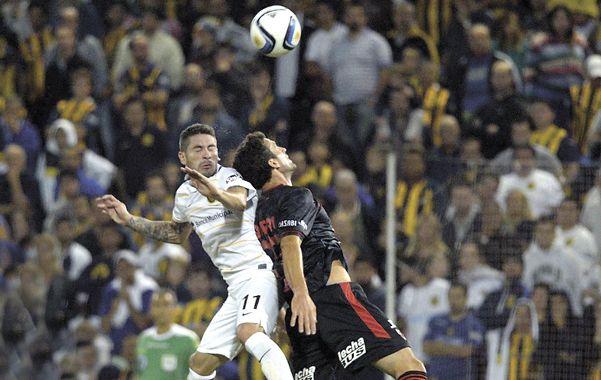 La pelota no fue bien tratada. José Luis Fernández la pelea en el salto con el sabalero Pablo Ledesma.