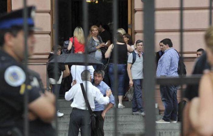 Trabajadores salen de la Casa Rosada tras haber sido despedidos sin previo aviso.