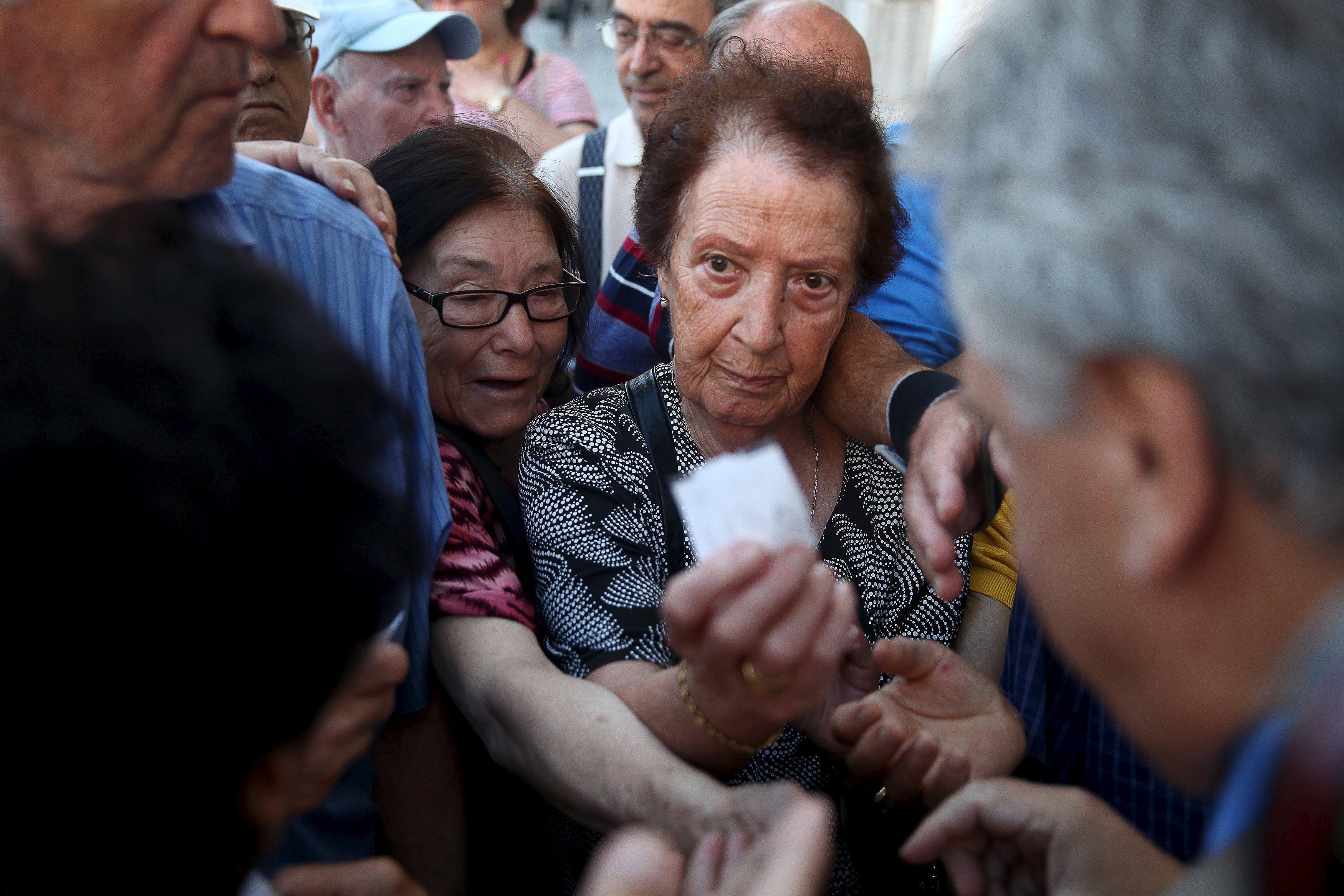angustia. Los jubilados griegos deben sacar número fuera de los bancos para cobrar sus haberes.