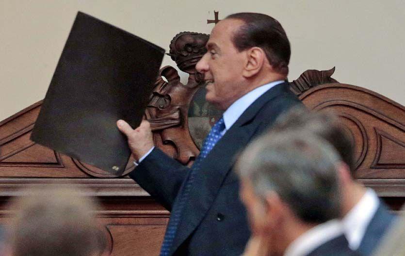 Al ataque. Berlusconi al reunirse ayer con sus legisladores en una sala del Parlamento en Roma.