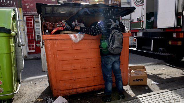 Dura realidad. Un muchacho busca alimentos dentro de un contenedor en la zona céntrica.