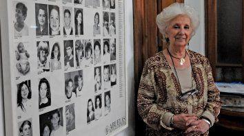 Estela de Carlotto en la sede de Abuelas.  Elige posar junto a la foto de los nietos y nietas recuperados, como un mensaje de amor y optimismo para transmitir en las aulas.