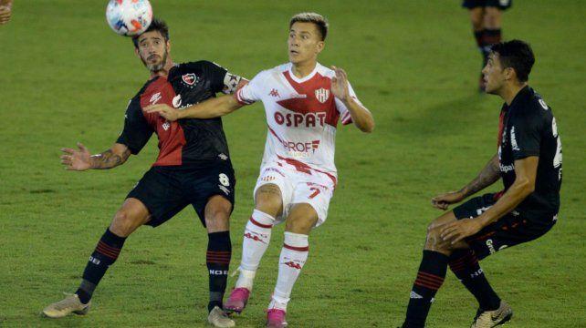 Pablo Pérez disputa la pelota con Cristián Insaurralde mientras Juan Pablo Freytes llega en apoyo.
