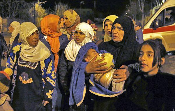 En fuga. Mujeres y chicos aprovechan la entrada de un convoy de ayuda para salir de Madaya.
