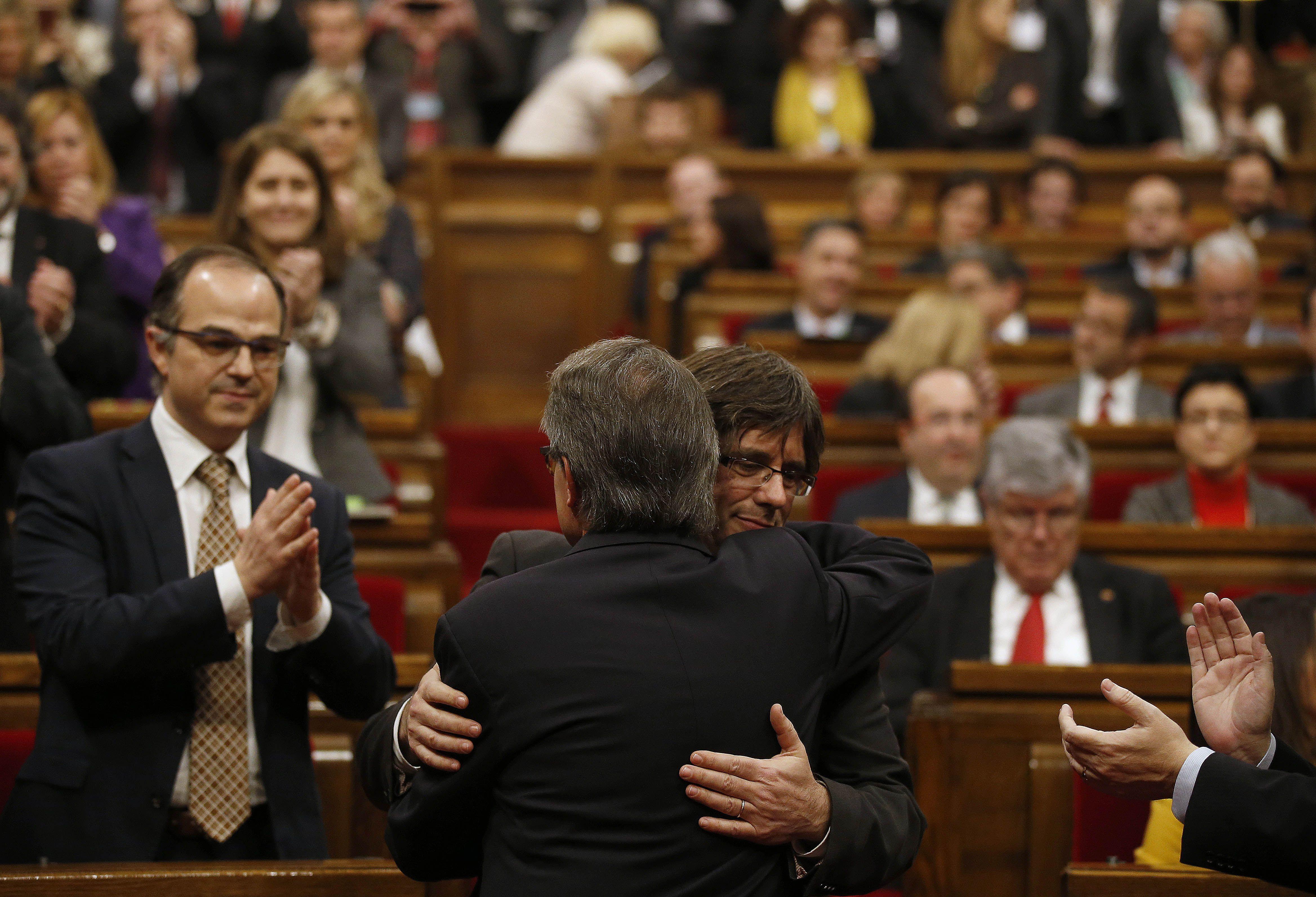 Artur Mas (de espaldas) se abraza con Carles Puigdemont en el Parlamento de Barcelona. (AP)